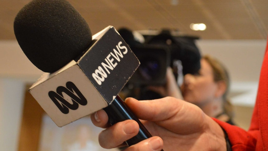 Close up of microphone with ABC News logo in hand with camera in the background.