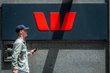A man holding his mobile phone walks past a Westpac Bank sign in George street Sydney on January 28 2019.