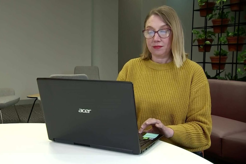 A woman at a table working on a laptop.