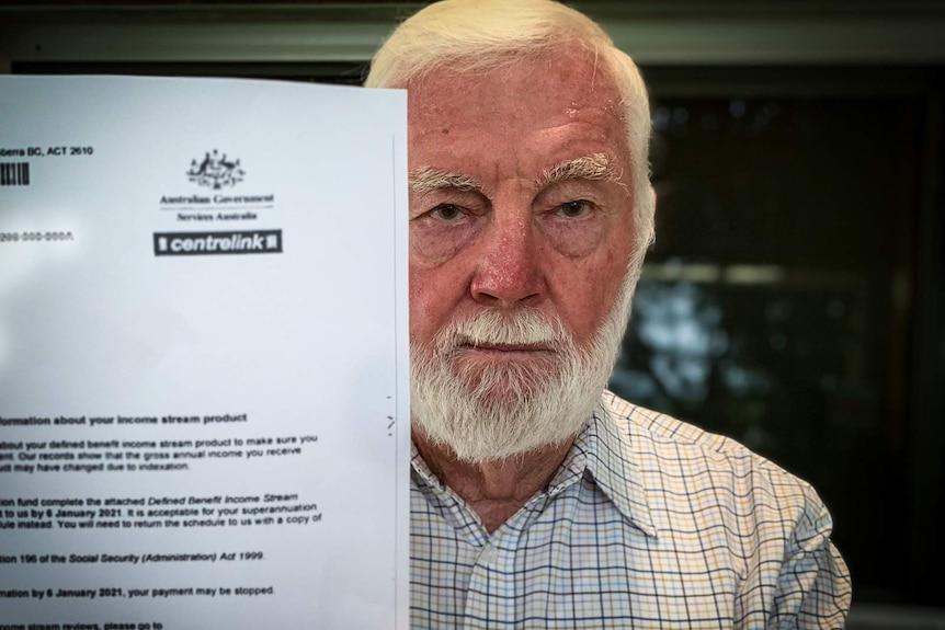 Man holds up letter from Centrelink