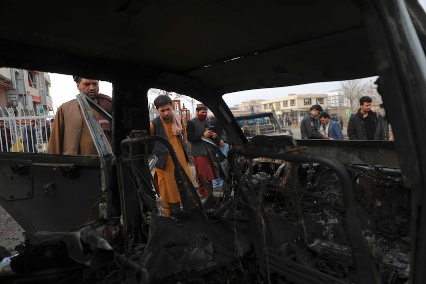 People look at the inside of a car that  has been burned out by the blast. The interior is completely blackened.
