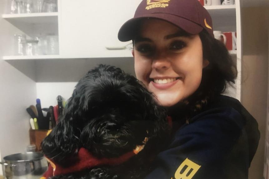Georgie Tunny in Brisbane Broncos gear with her dog.