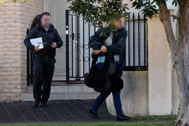 Two men wearing black and carrying bags walk away from the gate of a house.