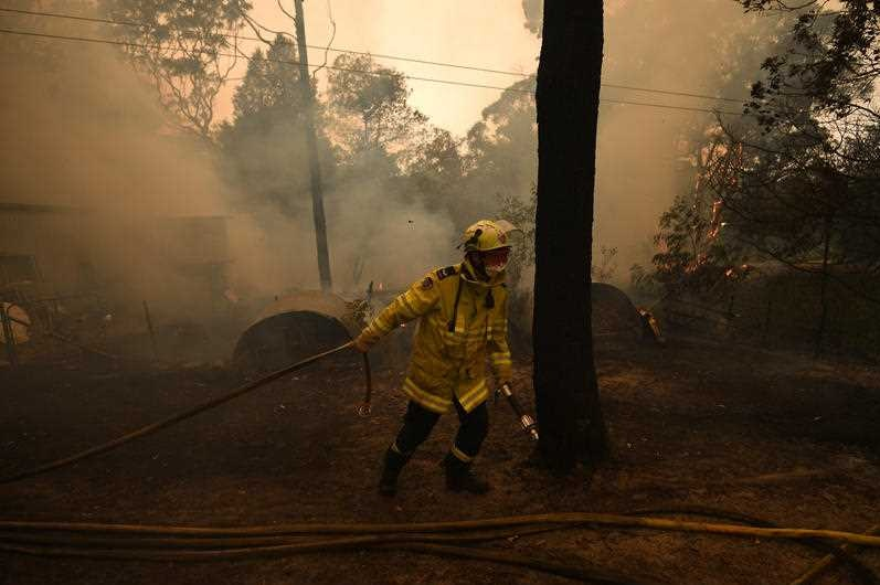 NSW RFS crews work to protect a property in Kulnura from the Three Mile fire.
