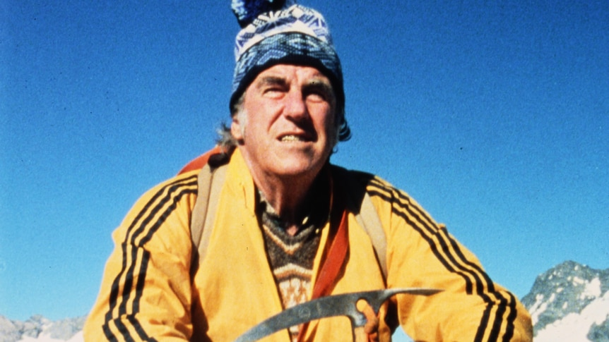 Close up of Sir Edmund Hillary wearing a blue beanie and yellow jacket.