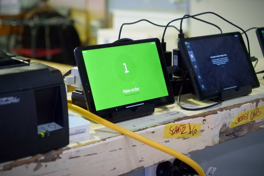 Tablet computer screens lined up on a bench top