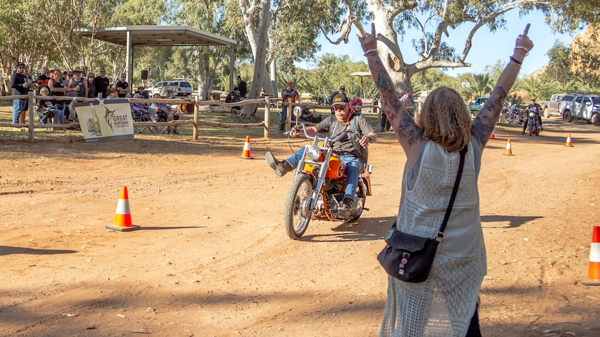woman with tattooed arms raised in the air watching a man on his orange motorbike navigate a short dirt obstacle course