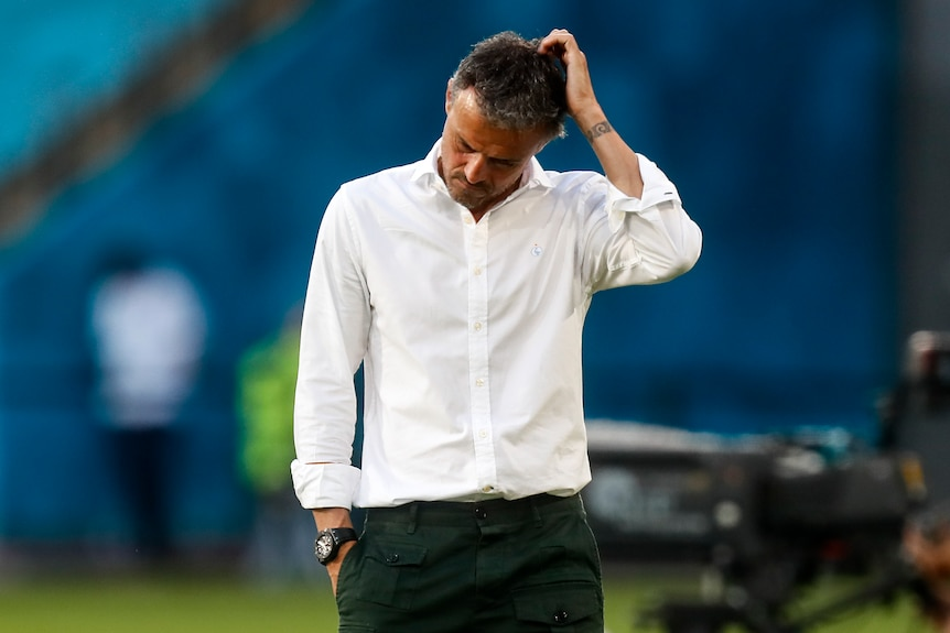 A Spanish team football manager runs his hand through his hair in frustration during a match at Euro 2020