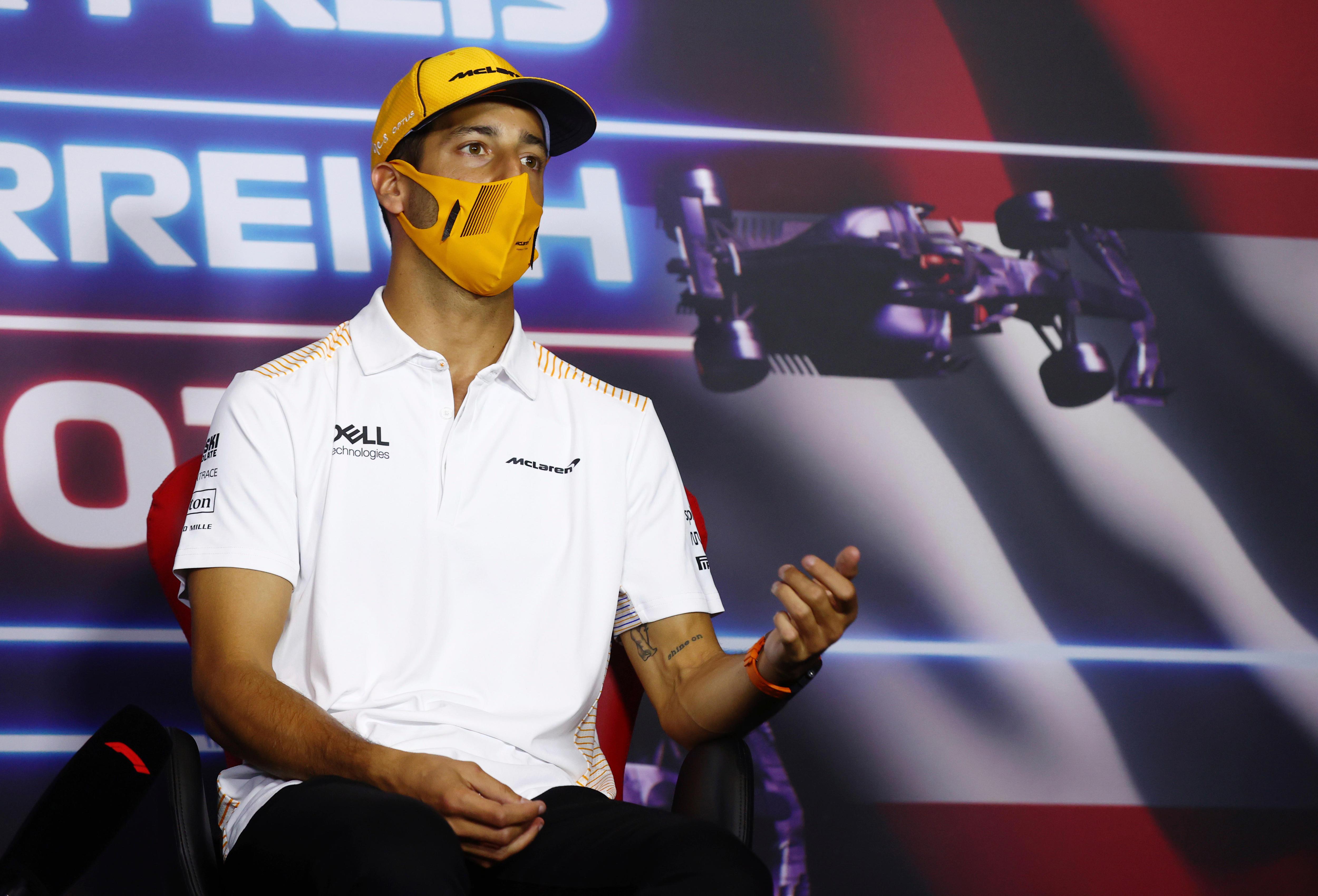 A mask-wearing Daniel Ricciardo gestures with his hand as he makes a point at an F1 press conference.