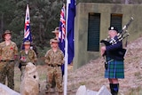 Army cadets and a musician outside of a historic world war two bunker for anzac day.