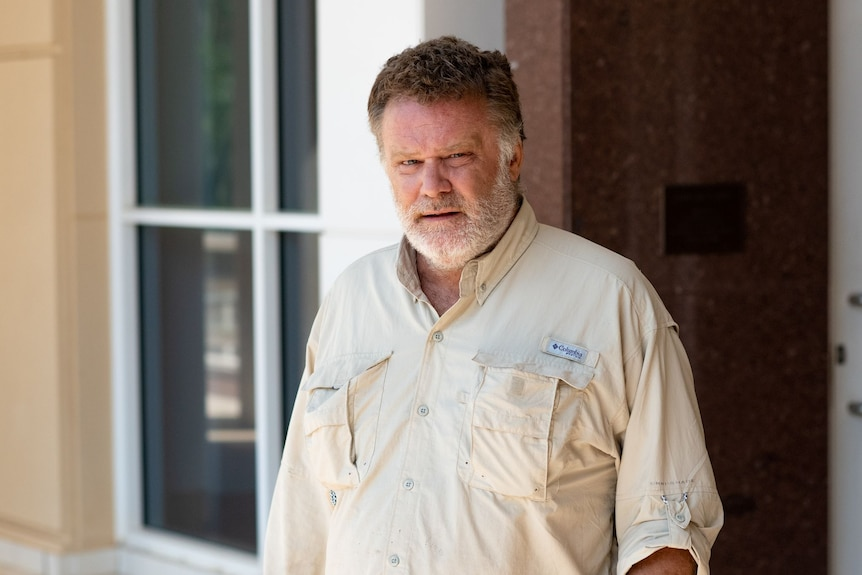 A white man wearing a button-up camping shirt leaves court.
