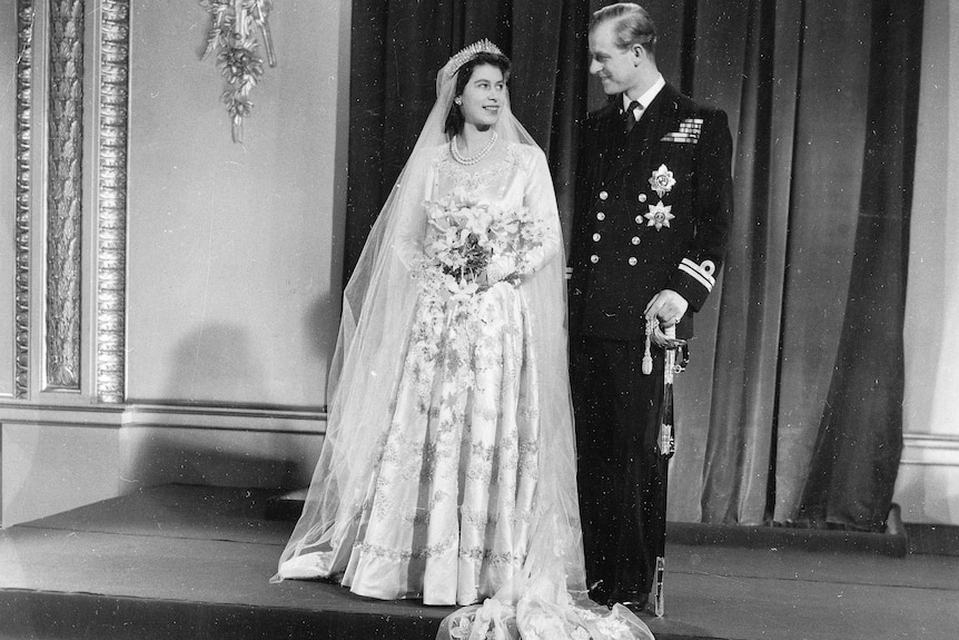 Queen Elizabeth and Prince Philip stand in their wedding outfits.