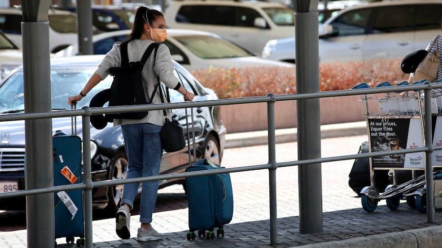A woman pulling a suitcase outside an airport wears a face mask.
