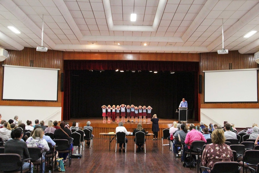 Children on a stage in front of judges and audience.