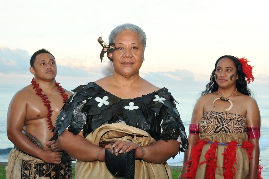 Fiame Naomi Mata'afa stands in front of a man and woman, all in traditional Samoan garments, on a beach at dusk.