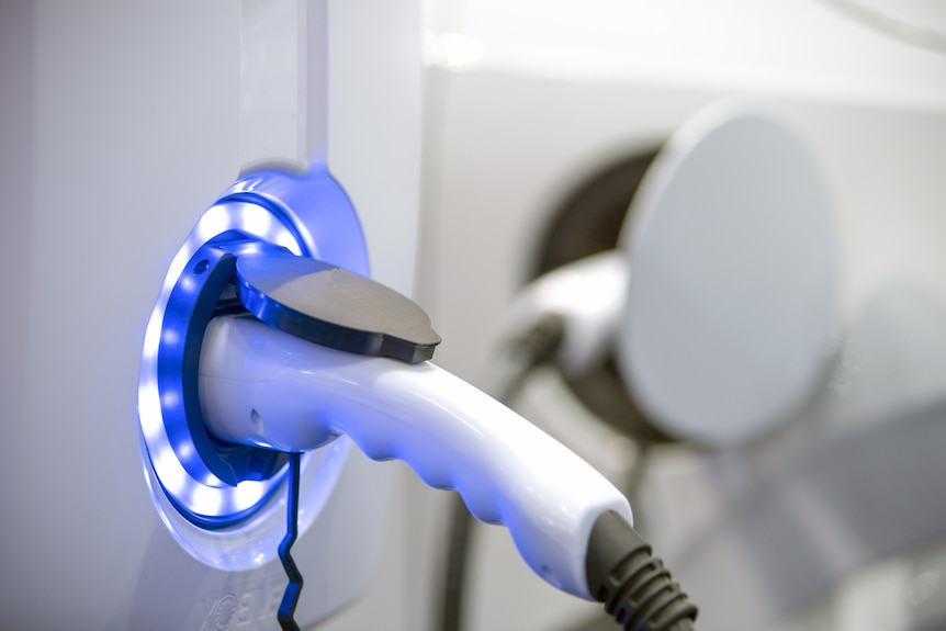 An EV plug surrounded by bright blue LEDs