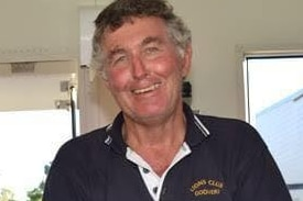 A man in his 60s with blue eyes, wearing blue collared shirt, smiling.