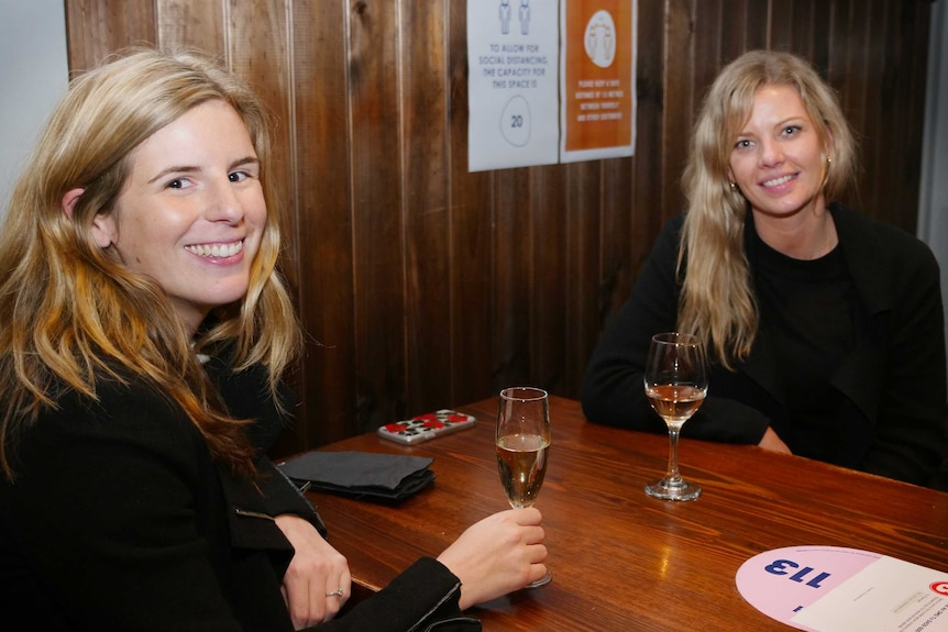 Two young women smile while sitting at a table with glasses of wine
