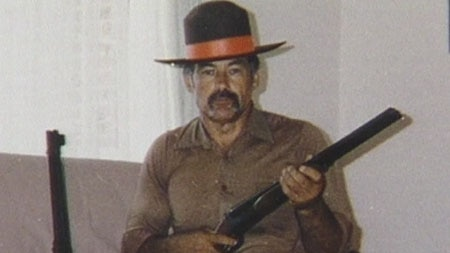 A young Ivan Milat holds a shotgun.