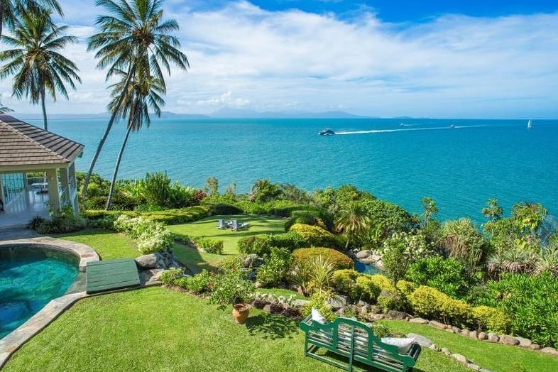 The spectacular view from a home perched on a hill overlooking the ocean with a catamaran crossing the water about 500m away