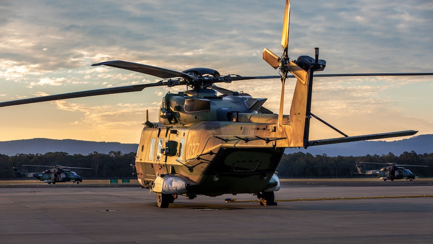 An army helicopter sits on the tarmac as the setting sun casts golden light across it from the left.