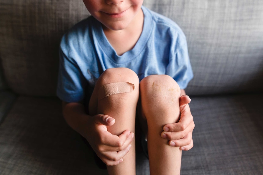 A young boy in a blue t-shirt smiles, holding his knees, one of which has a Band-Aid.
