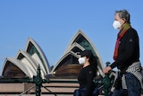 A man and a woman wearing masks walk past the Sydney Opera House.