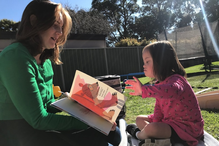 Woman reading a book to small girl in backyard.