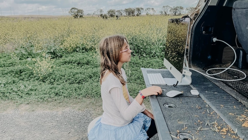 A young gild sits on a still at the back of a ute looking at a computer