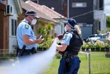 nsw police officers talking at either end of police tape