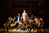 A scene from the musical Hamilton with the protagonist Alexander Hamilton standing on a box on a stage surrounded by the cast