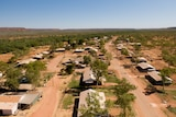 An aerial photo of houses and trees in a desert landscape.
