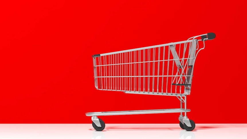 A metal shopping trolley against a red background.