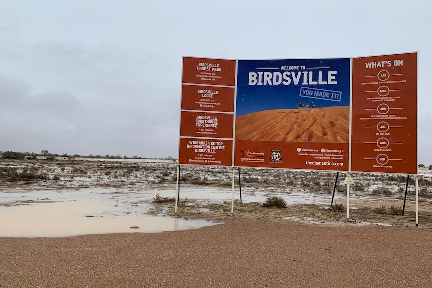 Large town sign in big puddle after rain