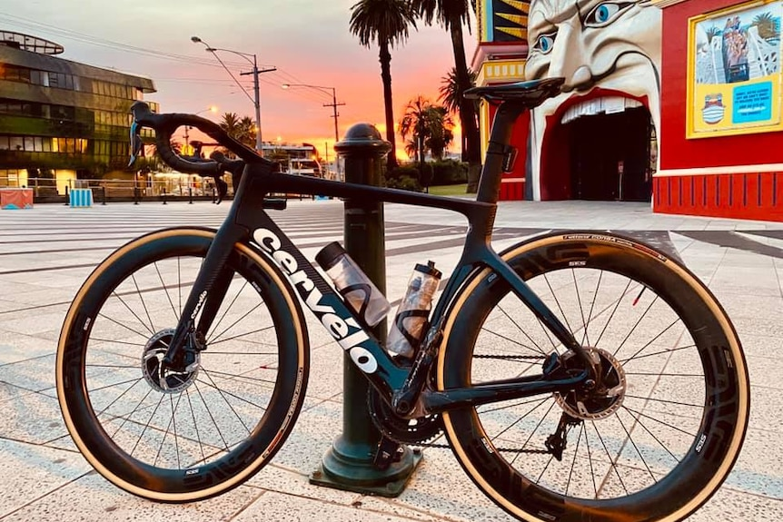 A bicycle rests on a post outside Lunar Park in Melbourne while the sun sets