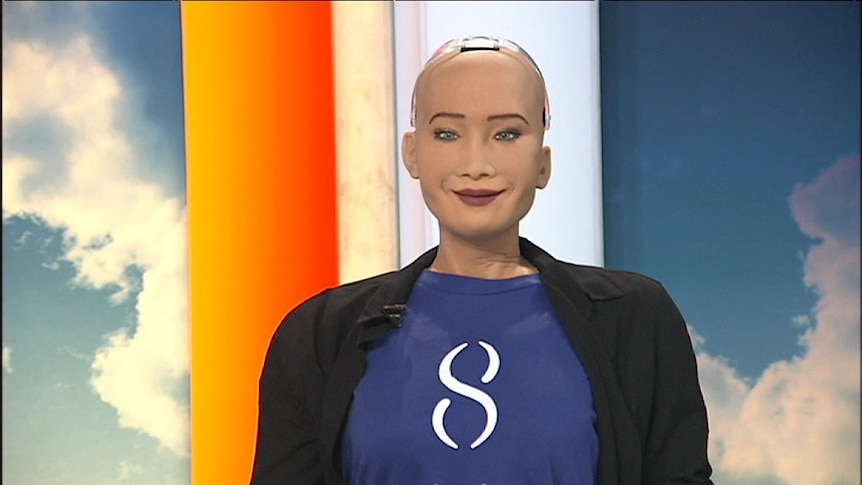 The torso of Sophia the robot sits at the news desk.