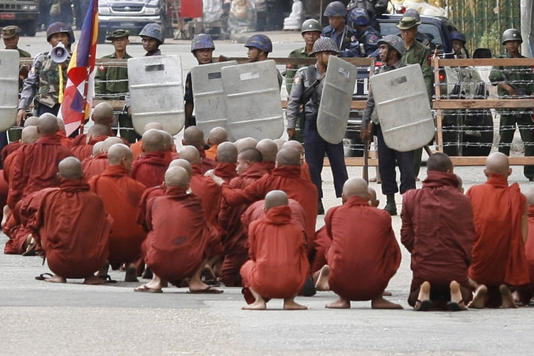 Monks sit infront of riot police in Burma