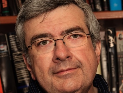 A man smiles toward the camera in front of a bookshelf.
