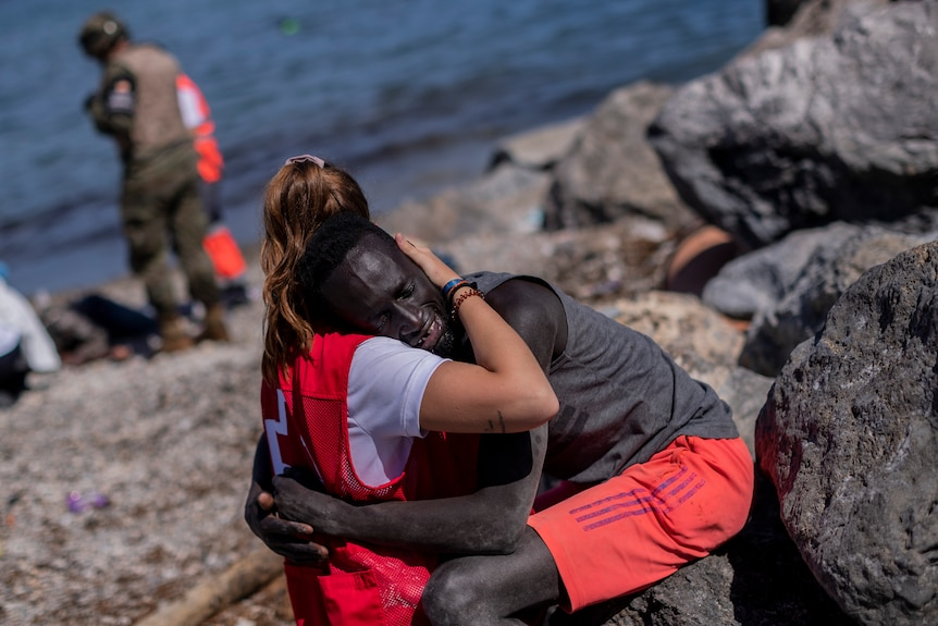 A migrant is comforted by a member of the Spanish Red Cross near the border of Morocco and Spain.