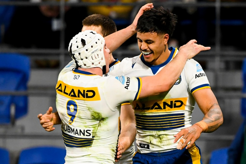 Two Parramatta Eels NRL players embrace as they celebrate a try against the Gold Coast.