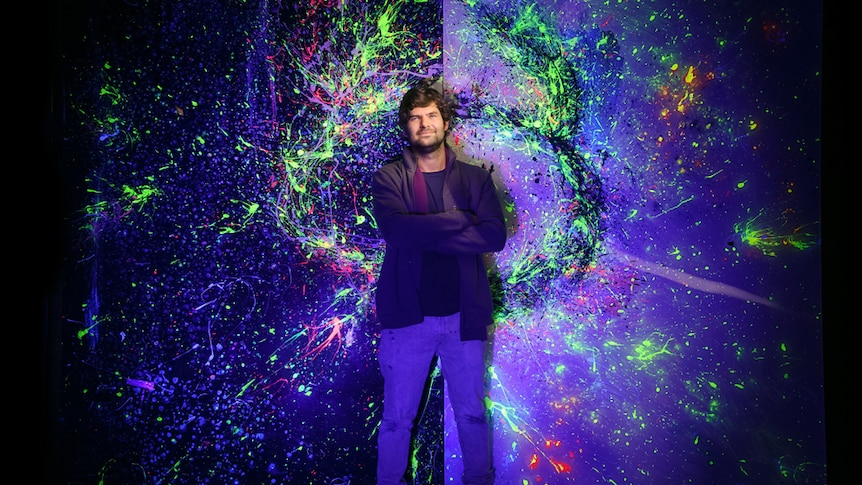 Man smiling against a large painting with luminescent colours.