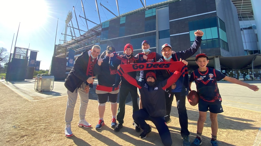A small group of people in Melbourne Demons colours smile happily outside the MCG on a sunny day.