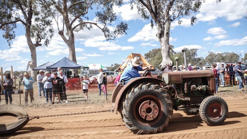 A tractor pulls a tyre while spectators watch on