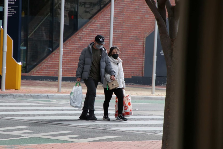 A couple wearing masks hold hands as they cross an empty road.