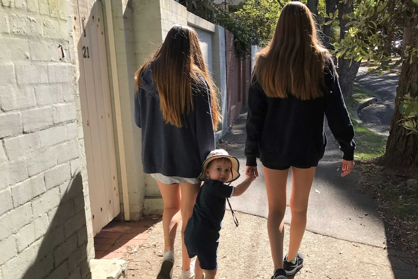 Two young teenage girls walking along a footpath holding hands with a toddler