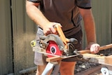An unidentified tradie cuts a piece of wood.