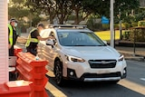 Police officers perform checks as car crosses newly reopened Queensland-NSW border bubble