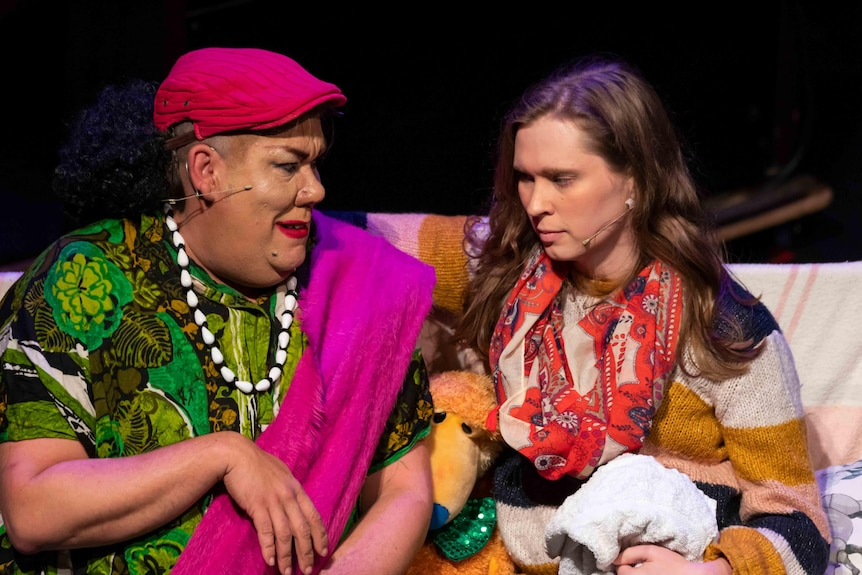 A colourful drag queen sits on a couch talking to a woman wearing a bright scarf.