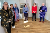 Group of older women standing in an empty kitchen.