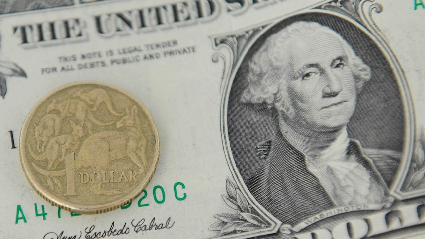 A gold coin, the Australian $1, sits on top of a US dollar note.